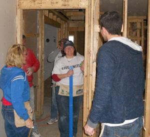 Wright State University Bookstore Manager Jennifer Gebhart working alongside Habitat for Humanity crew members.