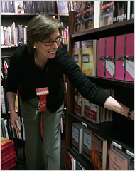 Nancie Scheirer, Trade Manager of the Harvard COOP, arranges books in the non-fiction section of the bookstore.