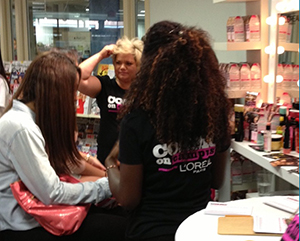Cosmo and L'Oreal representatives consult with a student from at the GMU Bookstore at George Mason University in Fairfax, Virginia.