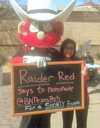 Texas Tech Bookstore Manager Monica Cowie poses with the school's mascot,  'The Masked Rider.""