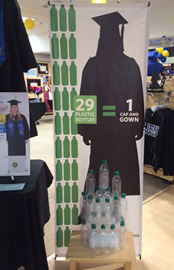 """A display at the Spartan Bookstore showing how many water bottles were used to create a """"green"""" graduation gown that students can order for commencement."""