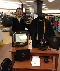 A display in the SUNY Cobleskill Bookstore showcases graduation regalia and gifts for graduates.
