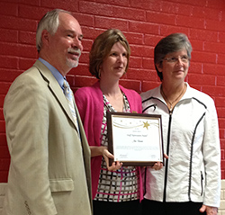 Vice President of Student Affairs Steven Ackerknecht and President Dr. Debra H. Thatcher present SUNY Cobleskill Bookstore Manager Jeri Usatch with an award for her service to the school.