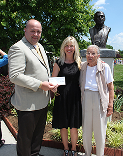VMI Keydet Bookstore Manager Neil Scarborough presents a check to The National D-Day Memorial Foundation President April Cheek-Messier at the dedication of the Bob Slaughter bronze bust on Memorial Day. In attendance is Slaughter's widow, Margaret Slaughter.
