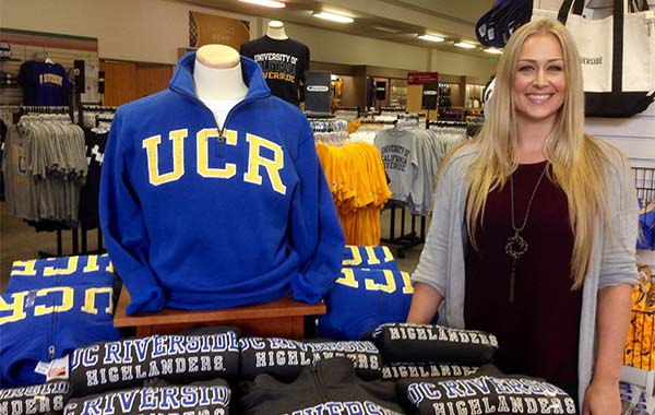Jaimi Yerkes, Merchandise Department Manager at the UCR Campus Store at the University of California Riverside, stands beside a display of official UCR sweatshirts in the new campus bookstore.