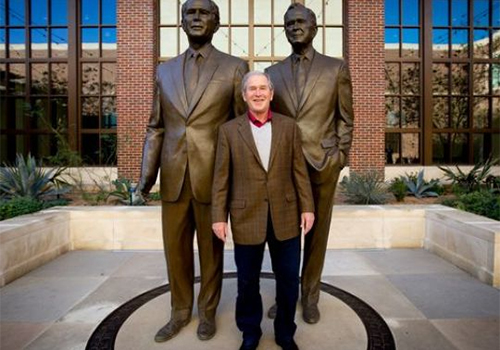 President George W. Bush with sculptures of him and his father in the courtyard at the George W. Bush presidential library in Dallas, Texas. (Photo: Allison V. Smith for USA TODAY)