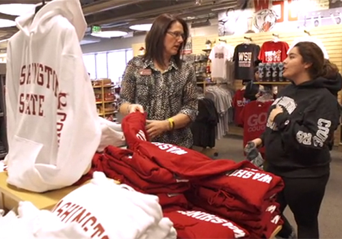 WSU Bookie Store Manager Leslie Martin helps a WSU student with Washington State apparel.