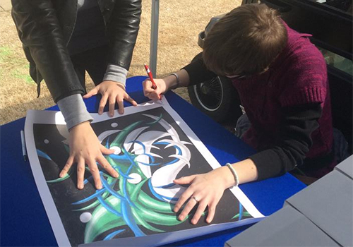 Georgia College graduate student, Kelly Self, signs copies of a limited edition print she created of the school's mascot.
