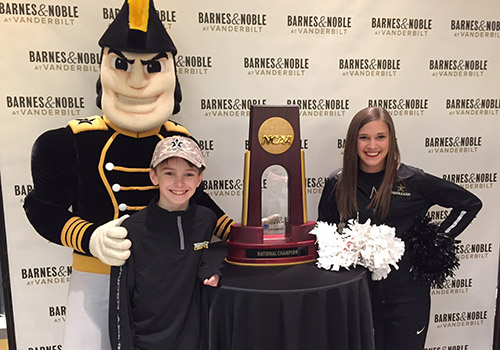 A young Vandy fan poses with Mr. C, Vanderbilt's mascot, a Vanderbilt cheerleader and the 2014 World Series Championship trophy at the Baseball Signing event held at the Barnes & Noble at Vanderbilt bookstore.