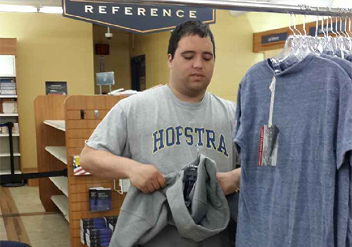An adult student from the Genesis Eden II program on Long Island works in the Hofstra University Bookstore tagging and sorting apparel.