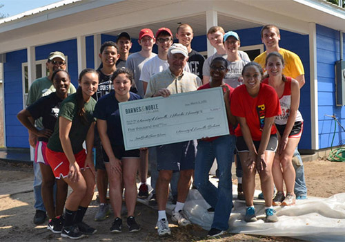 University of Louisville students stand in front of the house they worked on in Lake Sumter, Florida during their spring break.
