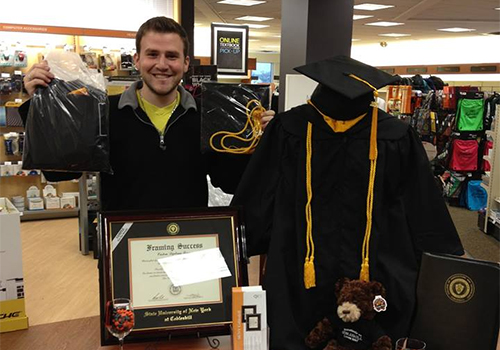 A SUNY Cobleskill student picks up his graduation regalia at the Grad Fair, held in the campus bookstore.