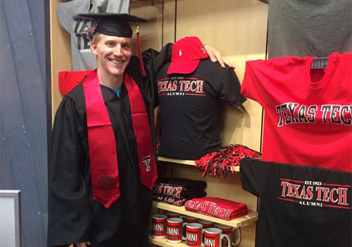 A Texas Tech University student models the graduation cap and gown at the Grad Fair, held at the Texas Tech Bookstore.