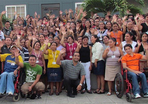 League Central America employees pose for a photos outside the factory they work in.