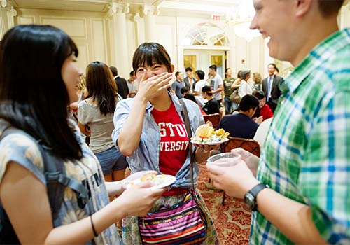 Riho Imada (from left), Akari Noguchi, and Andre Burwash enjoy refreshments at an International Student Reception. Photo by Jackie Ricciardi