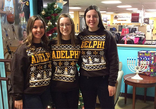 Adelphi University students show off their school ugly holiday sweater in the campus bookstore, located in Garden City, New York.