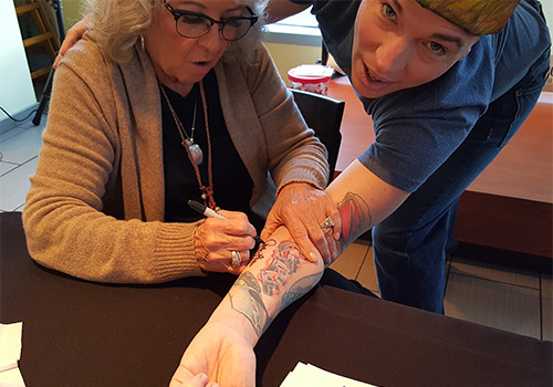 Fan C.J. Miller has is arm autographed by Deen with the intention of going directly to a tattoo parlor to ink her signature.