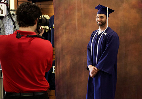 A student poses in his cap and gown at the Florida International University Bookstore located in __________
