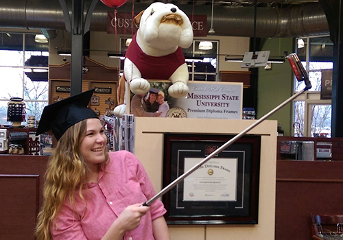 A Mississippi State University student takes a selfie with school mascot, Bully The Bulldog, at the MSU Grad Fair in Mississippi State, Mississippi.