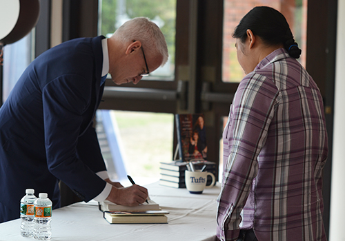 "Anderson Cooper signs a copy of his new book, ""Rainbow Comes and Goes: A Mother and Son on Life, Love, and Loss"" at his recent visit to Tufts University. Cooper was the guest speaker at this year's Edward R. Murrow Forum."