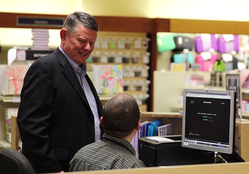 Providence College Bookstore Manager Joe Rushworth talks with a member of his staff.